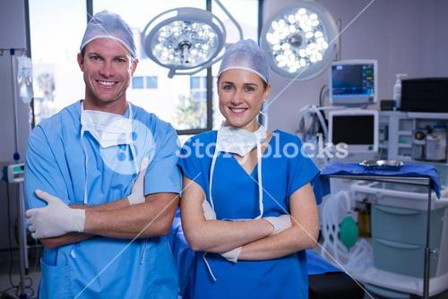 Portrait of male and female nurse standing in operation theater