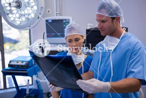 Male and female nurse examining x-ray in operation theater