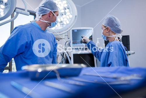 Male and female nurse using patien monitoring machine in operation theatert