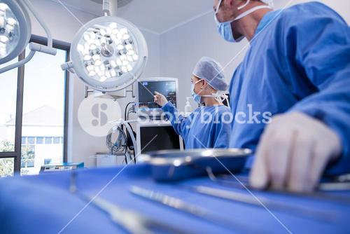 Male and female surgeon using patient monitoring machine in operation theater