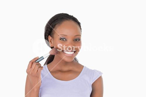 Close up of woman using makeup brush against a white background