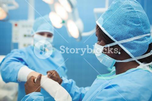 Female surgeon helping her co-worker in wearing surgical gloves