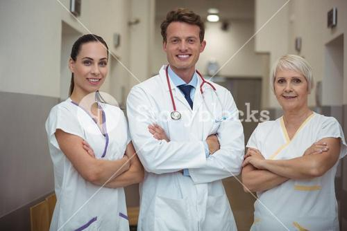 Portrait of doctor and nurse standing in corridor