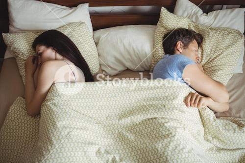 Couple sleeping back to back and ignoring each other on bed