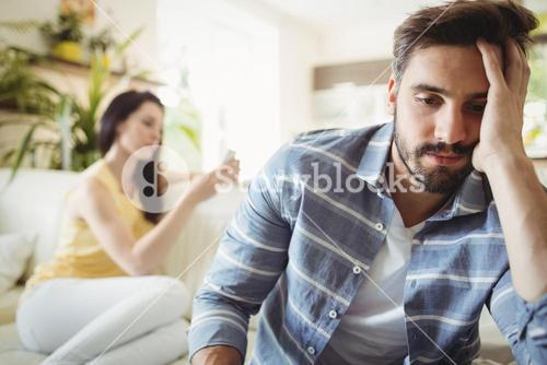 Upset couple ignoring each other on sofa