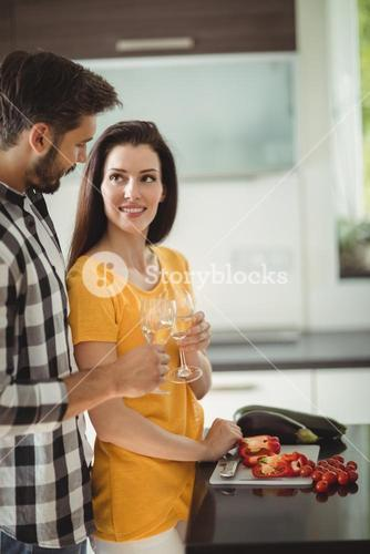 Happy couple toasting glasses of champagne while chopping vegetables in kitchen
