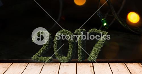 2017 in grass on wooden plank against a composite image 3D of christmas lights