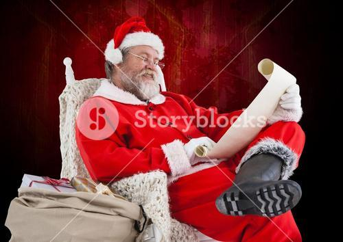 Santa claus sitting on a chair and reading wish list