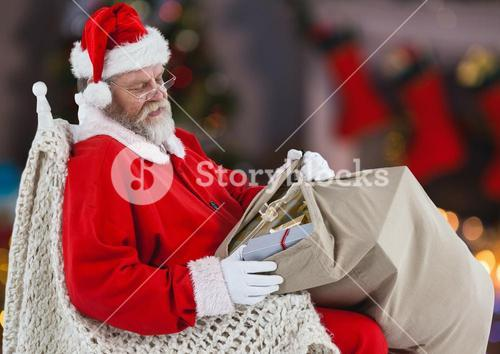 Santa claus with gift sack sitting on a chair