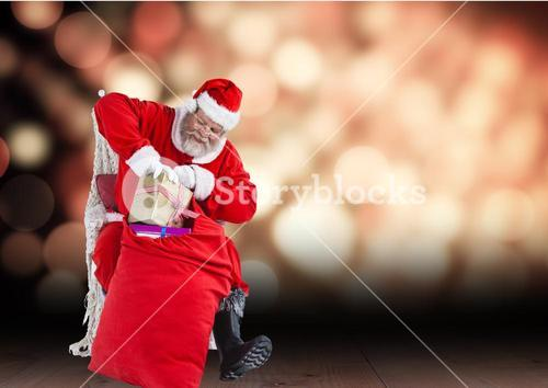 Santa claus removing gift from sack while sitting in chair