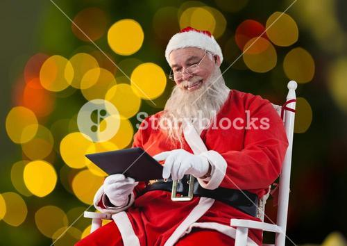 Santa sitting on chair and using digital tablet