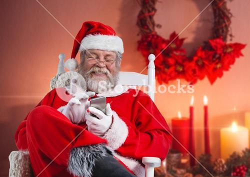 Happy santa sitting on chair and using mobile phone