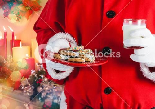 Santa hand holding cookies and a glass of milk