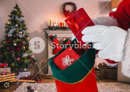 Santa putting gifts in christmas stocking in living room