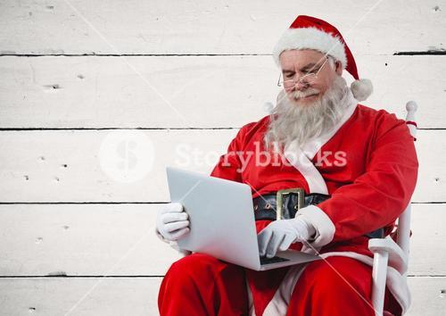 Santa sitting on chair and using laptop