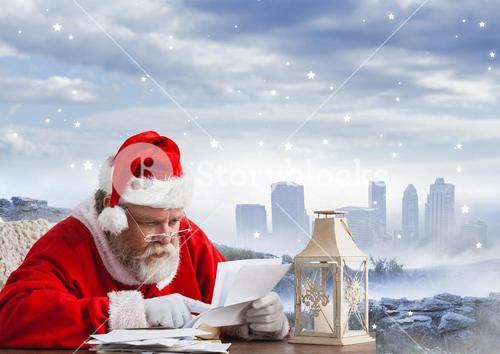 Santa sitting at table and reading christmas letter