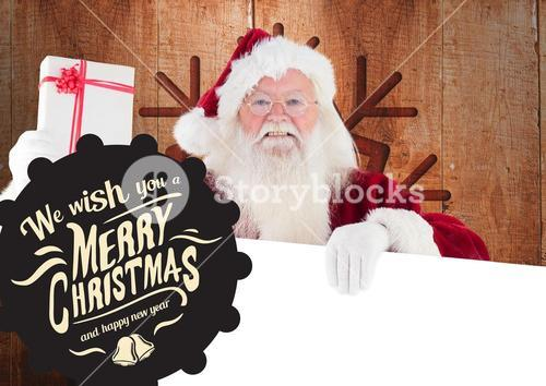 Merry christmas greetings against santa claus holding gift and placard