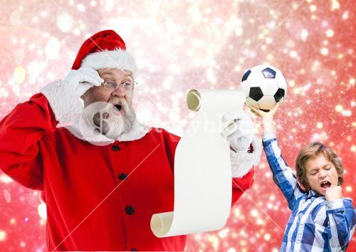 Santa claus reading wish list and excited boy with football