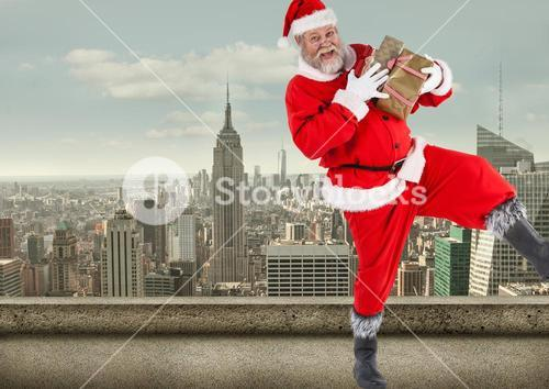 Santa claus  holding gift boxes standing on balcony of a building