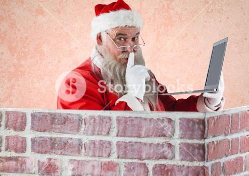 Santa claus with finger on lips holding a laptop