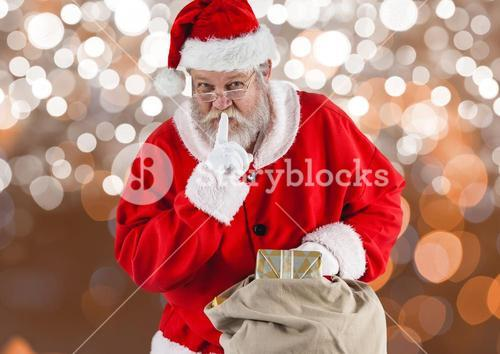 Santa claus with finger on lips holding gift bag