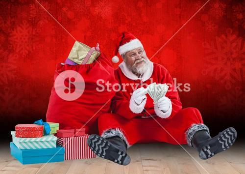 Santa claus holding banknotes sitting by gift bag