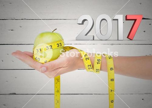 3D 2017 and hand holding green apple wrapped with measuring tape