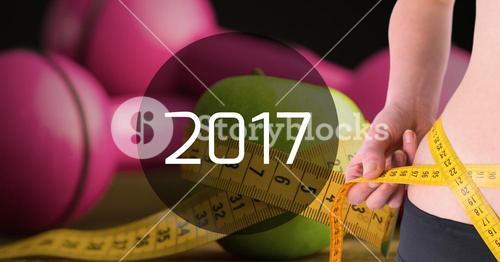Mid section of woman measuring her waist against 2017
