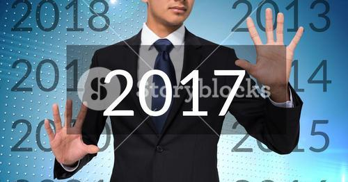Business man in digitally generated background touching 2017