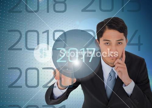 Thoughtful business man in digitally generated background touching 2017