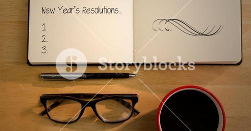 New year resolutions in book with spectacles, coffee mug and pen on table