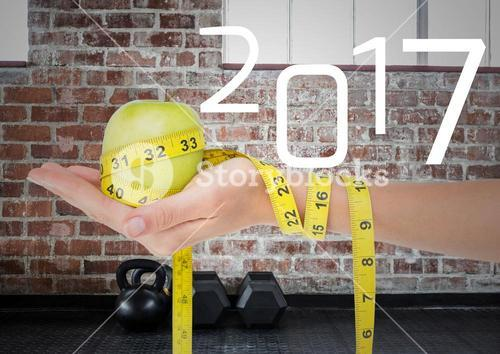Hand holding green apple wrapped with measuring tape against 2017