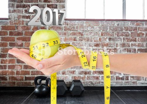 Hand holding green apple wrapped with measuring tape against 3D 2017