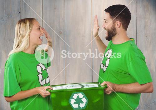 Couple wearing green recycling tshirts giving high five and holding box of recyclables