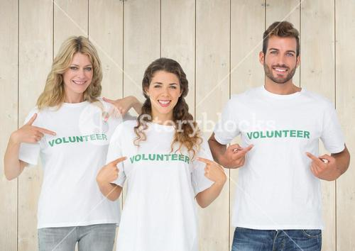 Three volunteer pointing at message printed on their tshirt
