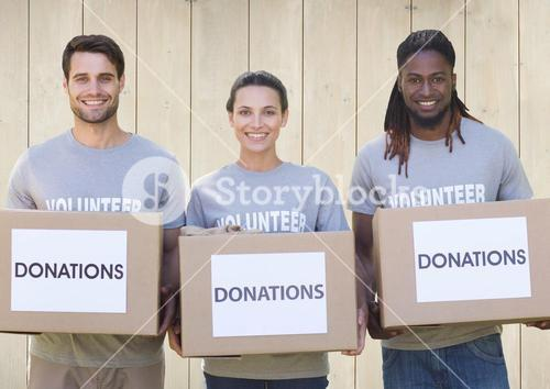 Three smiling volunteers holding donation boxes