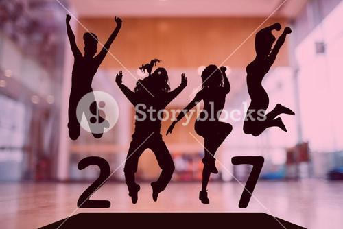 Silhouette of jumping people forming 2017 new year sign