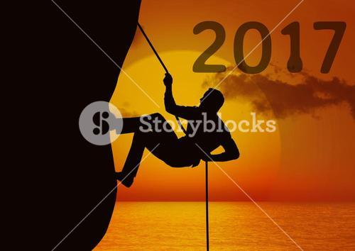 Composite image of 2017 with silhouette of man climbing a cliff using rope