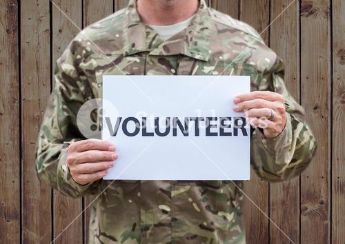 Person in camouflage uniform holding placard which reads volunteer