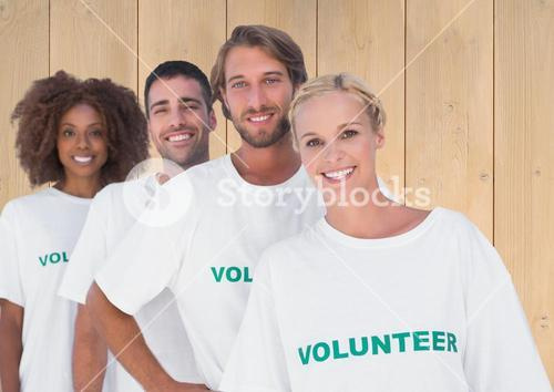 Group of volunteers standing against wooden background