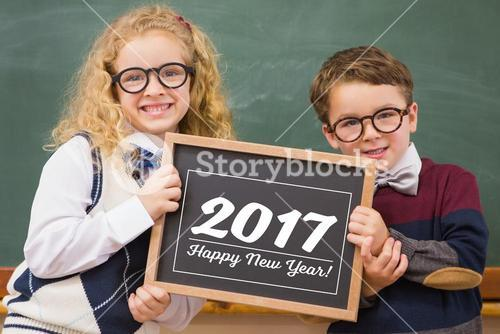 School kids holding chalkboard with new year text