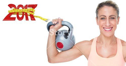 3D Composite image of happy female crossfitter lifting kettlebells looking at camera