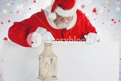 Composite image of santa claus holding christmas lantern on white board