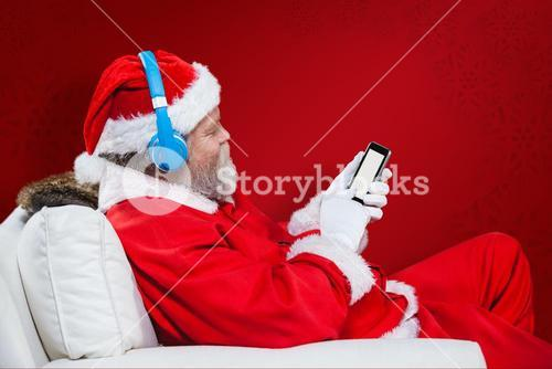 Composite image of santa claus using mobile phone with headphones