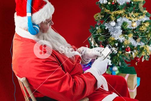 Composite image of santa claus using mobile phone with christmas tree