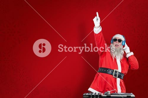 Composite image of santa claus playing dj with raised hand