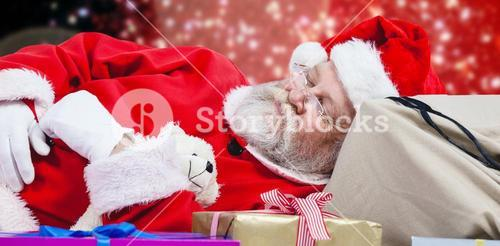 Composite image of close-up of tired santa claus sleeping beside christmas presents