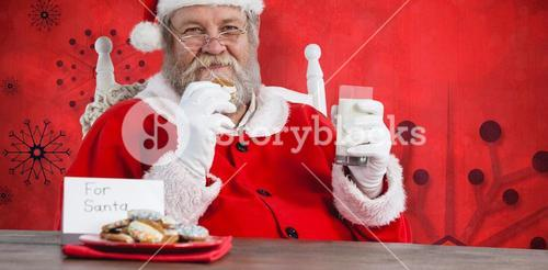 Composite image of santa claus holding glass of milk and cookie by table