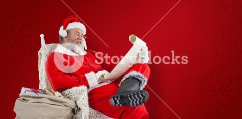 Composite image of santa claus reading wish list on scroll against white background
