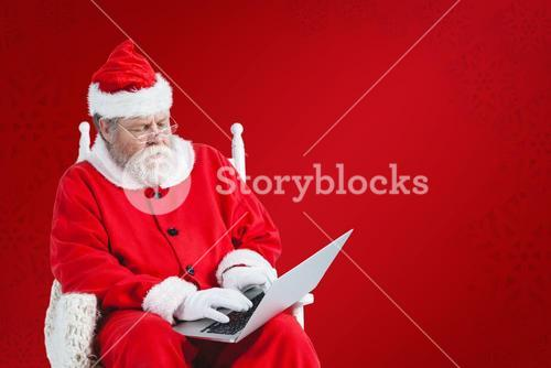 Composite image of serious santa claus using laptop